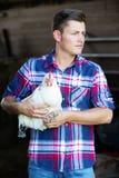 Agricoltore biondo bello che tiene un pollo bianco Fotografie Stock Libere da Diritti