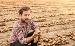 Agricoltore caucasico nel campo della cipolla di controllo della camicia di plaid Fotografie Stock