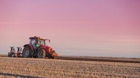 Agricoltore che ara campo al tramonto Immagine Stock