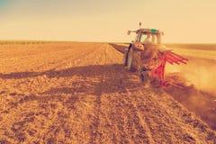 Agricoltore che ara campo di stoppie con il trattore rosso Immagini Stock