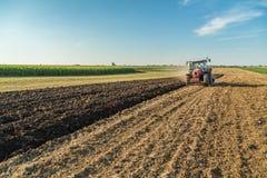 Agricoltore che ara campo di stoppie con il trattore rosso Immagine Stock