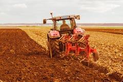 Agricoltore che ara campo di stoppie con il trattore rosso Fotografie Stock Libere da Diritti