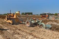Agricoltore che ara il campo con un vecchio trattore a cingoli Fiat Fotografie Stock Libere da Diritti