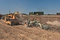 Agricoltore che ara il campo con un vecchio trattore a cingoli Fiat Immagini Stock