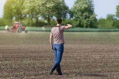 Agricoltore che cammina con la zappa Fotografia Stock