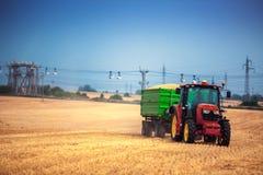 Agricoltore che conduce trattore agricolo e rimorchio in pieno di grano Fotografia Stock
