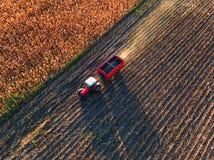 Agricoltore che conduce trattore agricolo e rimorchio in pieno di grano Immagini Stock Libere da Diritti