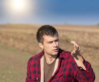 Agricoltore che esamina piantina nel campo Fotografia Stock