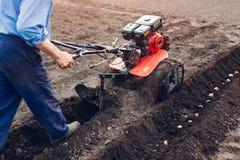 Agricoltore che guida piccolo trattore per coltivazione del suolo e la piantatura della patata Preparazione della primavera fotografie stock libere da diritti