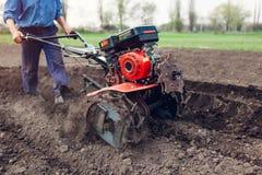 Agricoltore che guida piccolo trattore per coltivazione del suolo e la piantatura della patata Preparazione della primavera immagini stock libere da diritti