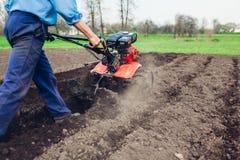 Agricoltore che guida piccolo trattore per coltivazione del suolo e la piantatura della patata Preparazione della primavera fotografia stock libera da diritti