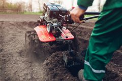 Agricoltore che guida piccolo trattore per coltivazione del suolo e la piantatura della patata Preparazione della primavera immagine stock