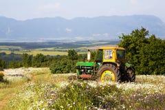 Agricoltore che guida un trattore attraverso un campo Fotografie Stock Libere da Diritti