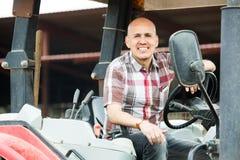Agricoltore che lavora al macchinario agricolo Fotografia Stock