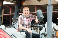 Agricoltore che lavora al macchinario agricolo Immagini Stock