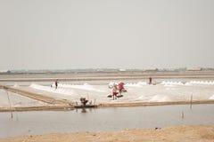 Agricoltore che lavora al mucchio del sale in Tailandia Fotografia Stock