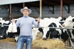 Agricoltore che lavora all'azienda agricola con le mucche da latte Fotografie Stock Libere da Diritti
