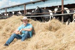 Agricoltore che lavora all'azienda agricola con le mucche da latte Fotografie Stock