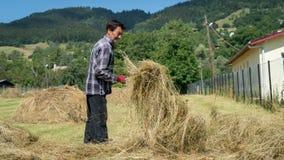 Agricoltore che lavora con i mucchi di paglia nell'azienda agricola aperta del campo, Artvin, Turchia immagini stock libere da diritti