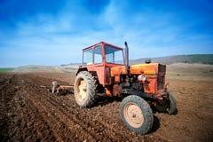 Agricoltore che lavora i campi con il trattore e l'aratro Fotografie Stock Libere da Diritti