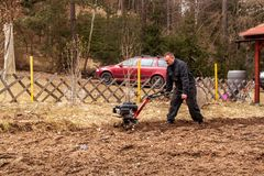 Agricoltore che lavora nel campo Lavoro della primavera sull'azienda agricola Uomo che ara il giardino Fotografie Stock