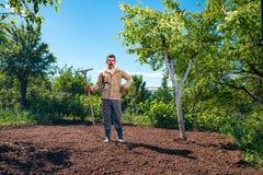 Agricoltore che lavora nel giardino per mezzo di un rastrello che livella il pl Fotografia Stock