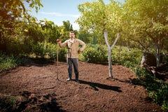 Agricoltore che lavora nel giardino per mezzo di un rastrello che livella il pl Fotografie Stock Libere da Diritti