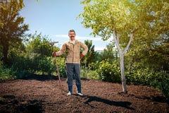 Agricoltore che lavora nel giardino per mezzo di un rastrello che livella pianta Immagini Stock