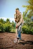 Agricoltore che lavora nel giardino per mezzo di una pala che scava t Fotografie Stock Libere da Diritti