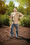 Agricoltore che lavora nel giardino per mezzo di una pala che scava t Fotografia Stock Libera da Diritti