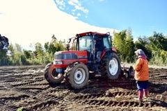 Agricoltore che lavora nell'azienda agricola con la mietitrice nel Giappone Kagoshima Sakurajima Immagine Stock Libera da Diritti