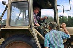 Agricoltore che parla con la gatto-sbucciatrice, che si siede in carrozza del trattore Fotografia Stock