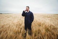 Agricoltore che parla sul telefono cellulare nel campo Fotografie Stock