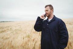 Agricoltore che parla sul telefono cellulare nel campo Fotografia Stock