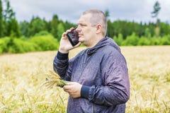 Agricoltore che parla sul telefono cellulare vicino al giacimento di cereale Immagine Stock