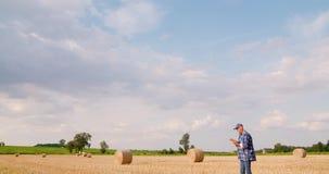 Agricoltore che per mezzo della compressa digitale mentre esaminando campo stock footage