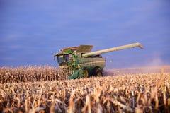 Agricoltore che per mezzo di una mietitrebbiatrice per raccogliere mais Immagine Stock