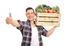 Agricoltore che porta una cassa e che dà un pollice su Immagini Stock