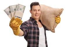 Agricoltore che posa con i pacchi del sacco e dei soldi della tela da imballaggio Fotografia Stock