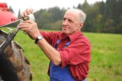 Agricoltore che ripara il suo trattore rosso Immagini Stock