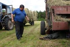 Agricoltore che ripara trattore nel campo, durante il fieno Immagine Stock