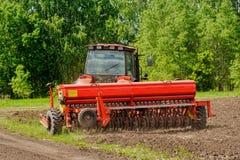 Agricoltore che semina i raccolti sul trattore al campo La Russia Immagine Stock Libera da Diritti