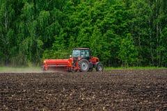 Agricoltore che semina i raccolti sul trattore al campo La Russia Fotografia Stock Libera da Diritti