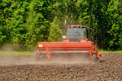 Agricoltore che semina i raccolti sul trattore al campo La Russia Fotografia Stock