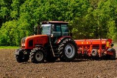 Agricoltore che semina i raccolti sul trattore al campo La Russia Fotografie Stock