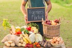 Agricoltore che sta alla sua stalla e che tiene lavagna Fotografia Stock Libera da Diritti