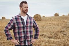 Agricoltore che sta con le mani sulle anche nel campo Fotografia Stock Libera da Diritti