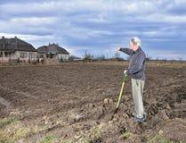Agricoltore che sta con una pala sul campo Fotografia Stock Libera da Diritti