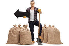 Agricoltore che sta fra i sacchi della tela da imballaggio con la pala e la freccia Fotografia Stock