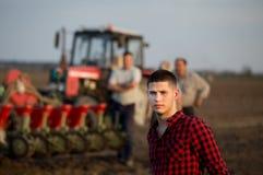 Agricoltore che sta nel campo con il trattore Fotografie Stock Libere da Diritti